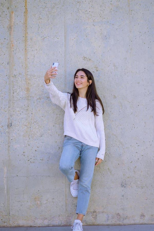 Selfie-Manie! Aufgeregtes junges Mädchen macht ein Foto mit Smartphone draußen - Bild lizenzfreie stockbilder