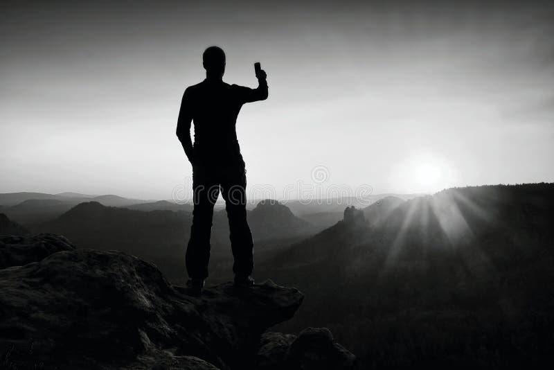 Selfie-Manie Großer Mannwanderer macht selfie Foto durch intelligentes Telefon auf Spitze des Berges bei Sonnenaufgang lizenzfreies stockbild