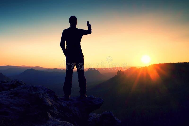 Selfie-Manie Großer Mannwanderer macht selfie Foto durch intelligentes Telefon auf Spitze des Berges bei Sonnenaufgang stockfoto