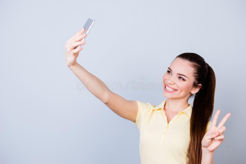 Selfie-Manie! Junger netter Brunette in einem zufälligen gelben T-Shirt lizenzfreie stockfotos