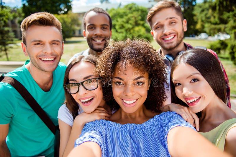 Selfie-Manie! Sechs internationale Studenten mit strahlendem Lächeln sind lizenzfreie stockfotografie