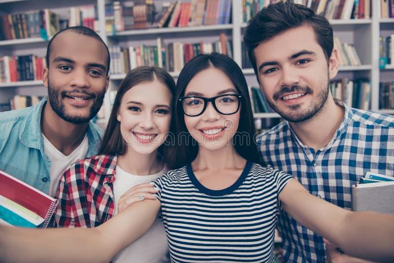 Selfie-Manie! Vier internationale Studenten mit strahlendem Lächeln AR lizenzfreies stockbild