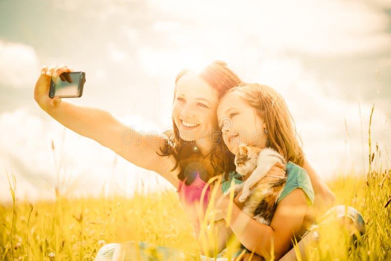 Selfie - moder, barn och kattunge royaltyfria bilder