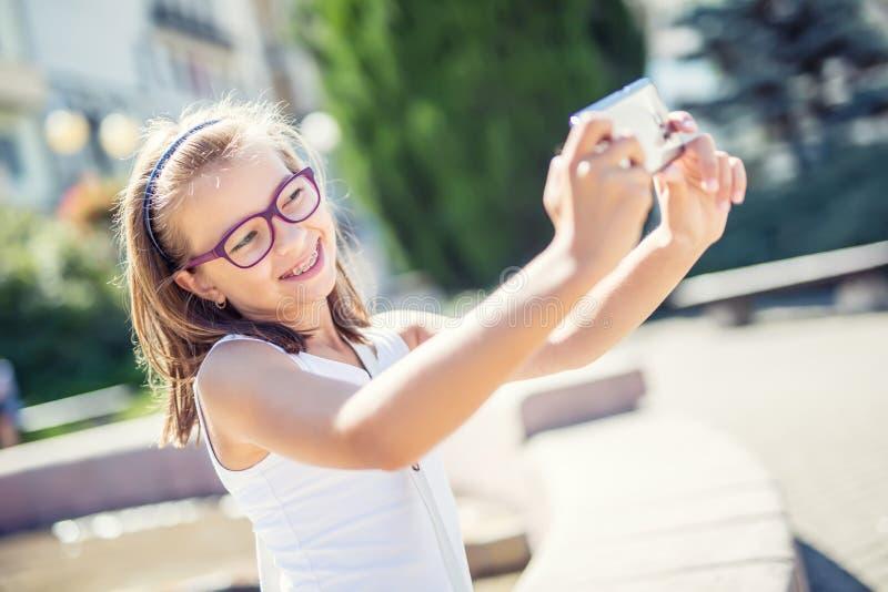 Selfie Mooi leuk jong meisje die met steunen en glazen voor een selfie lachen stock foto
