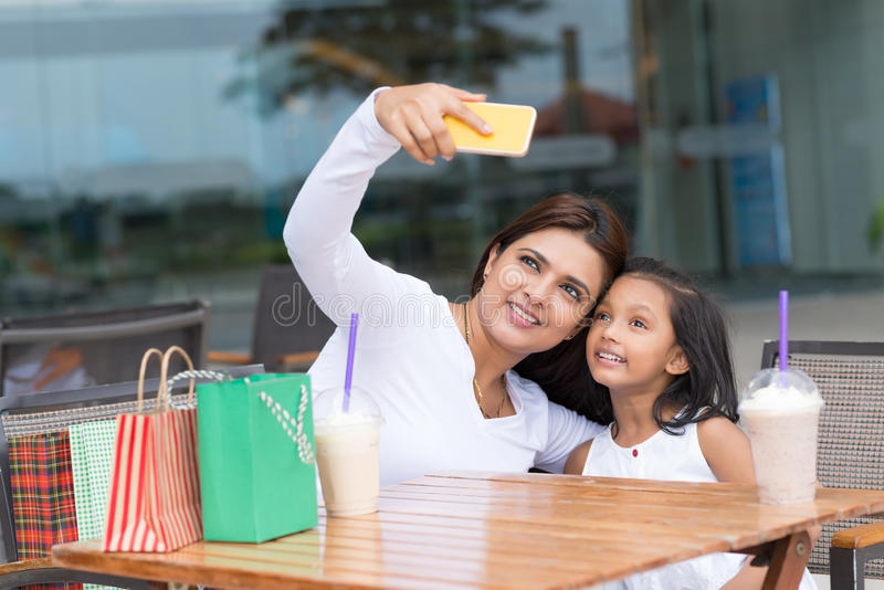 Selfie. Mother and daughter talking selfie after shopping stock photography