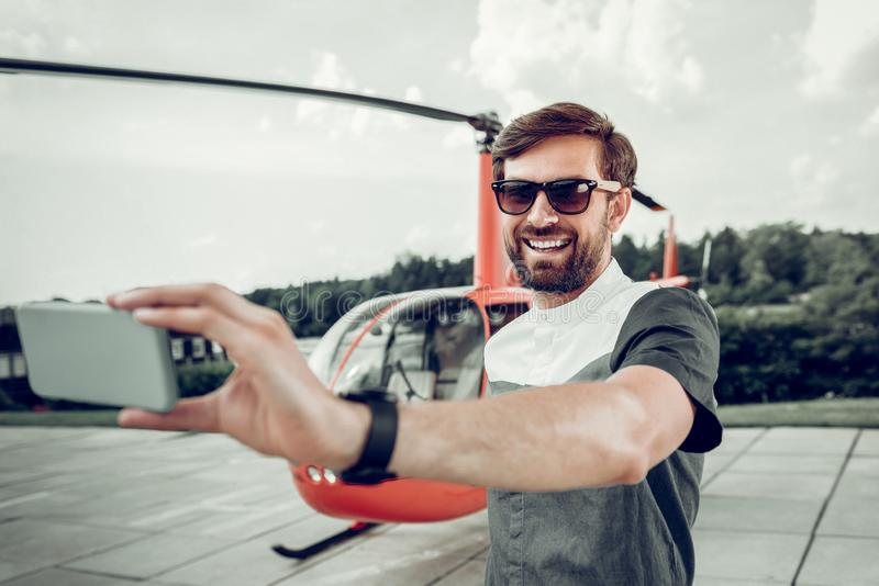 Handsome beaming businessman making selfie near private helicopter royalty free stock photography