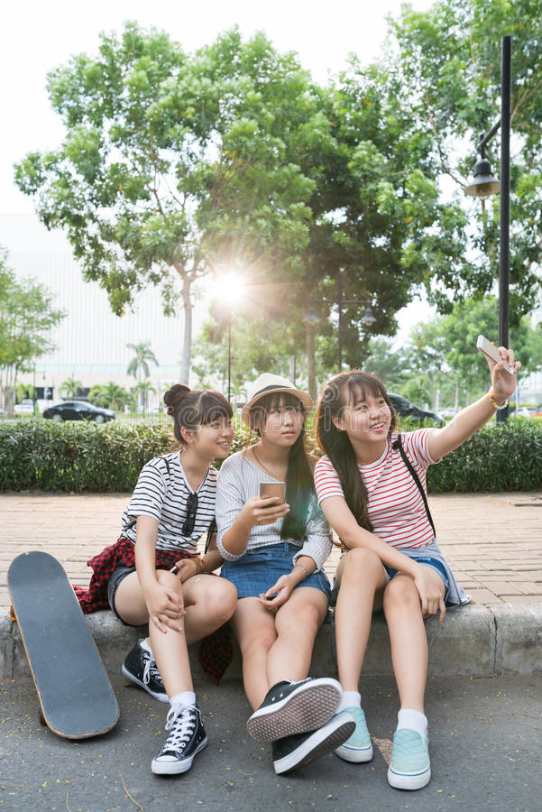 Selfie on pavement. Vietnamese schoolgirls sitting on the pavement and taking selfie royalty free stock photos