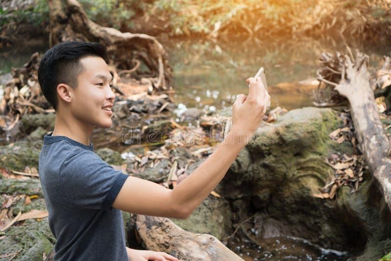 Selfie Photo: Asiatisk ung man som har smartphone för seleds på skog, vacker skola för peachful på våren. royaltyfria foton