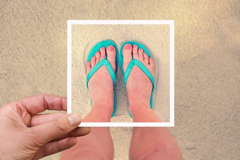 Selfie photo of woman feet wearing flip flops on a beach. Vintage process stock photography
