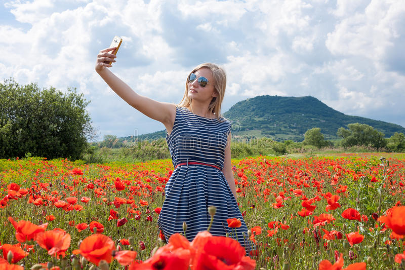 Selfie in the poppy field. Young girl wearing sunglasses and blue stripped cloth taking a selfie in a poppy field stock photos