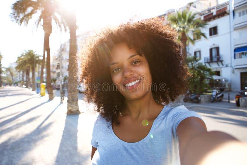 Selfie-Porträt der Frau draußen lächelnd mit dem gelockten Haar stockbild