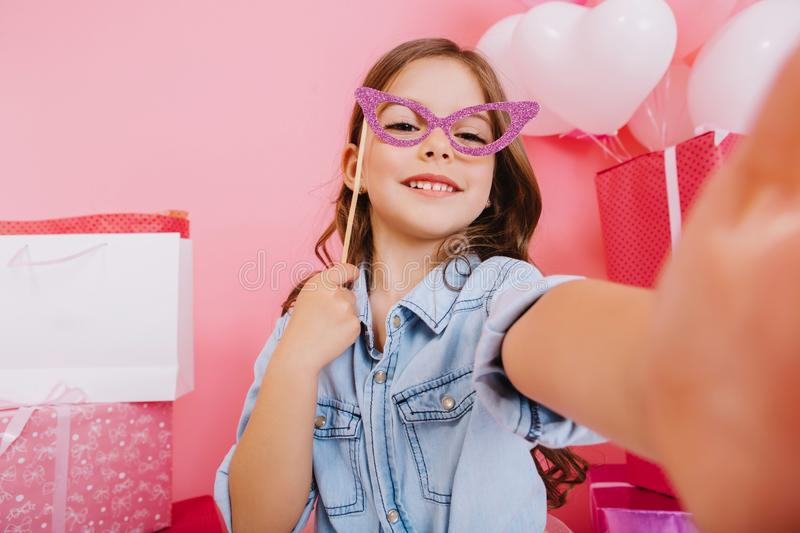 Selfie portrait amazing little girl with purple mask on face smiling to camera on pink background. Celebrating happy royalty free stock photography