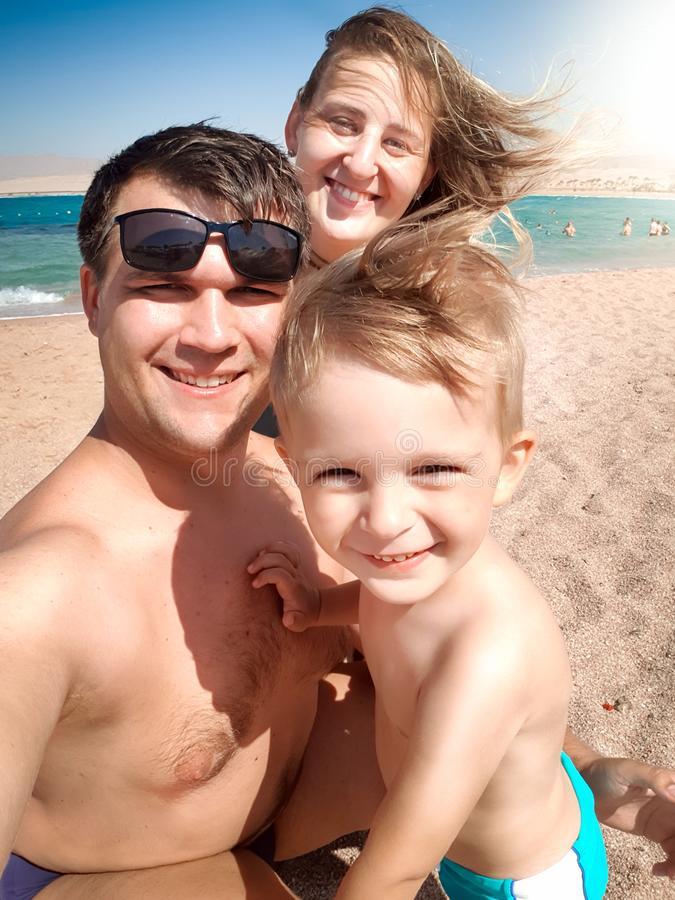 Selfie portrait of happy smiling cheerful family on the sea beach at sunny windy day. Family relaxing and having good royalty free stock images