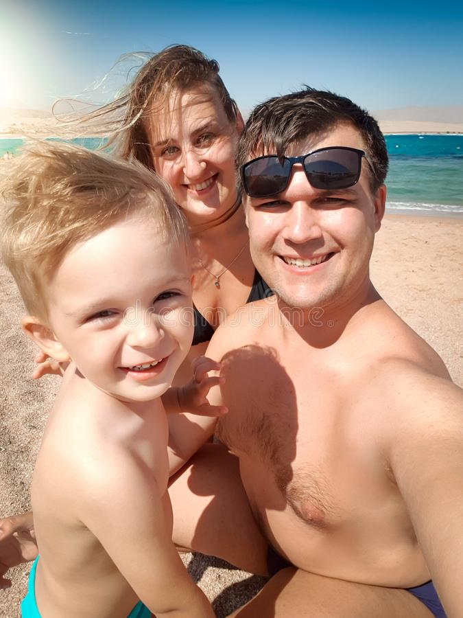 Selfie portrait of happy smiling mother, father and little son making selfie photo on sea beach. Family relaxing and stock photography
