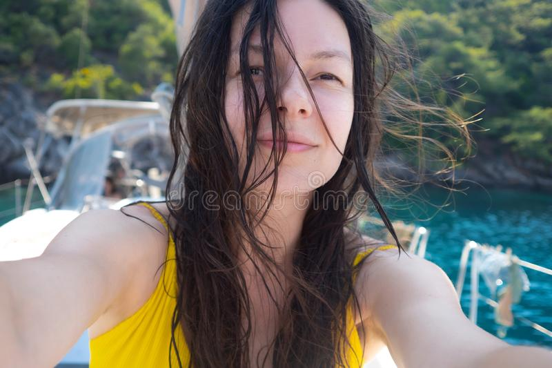 Selfie portrait of a positive multi-ethnic girl in a yellow swimsuit. stock images