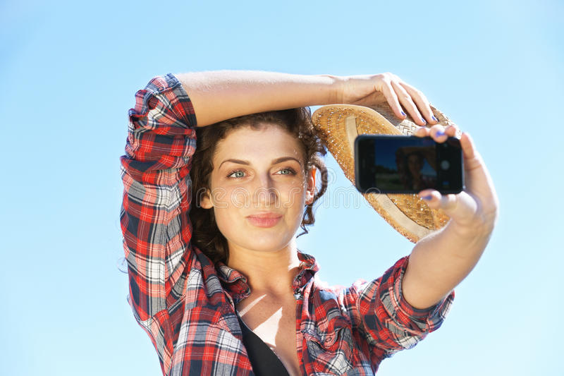 Selfie. Pretty woman taking selfie covering with the hat royalty free stock photos