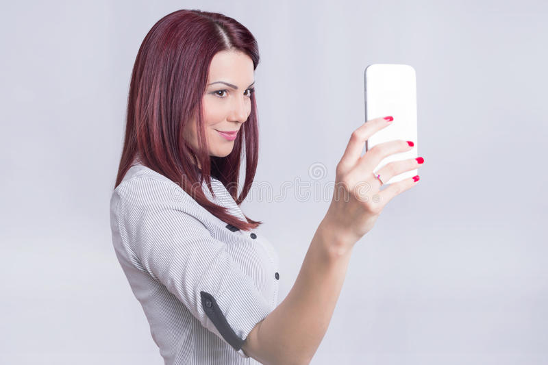 Selfie redhead. Redhead girl taking a selfie on her phone in studio stock photography