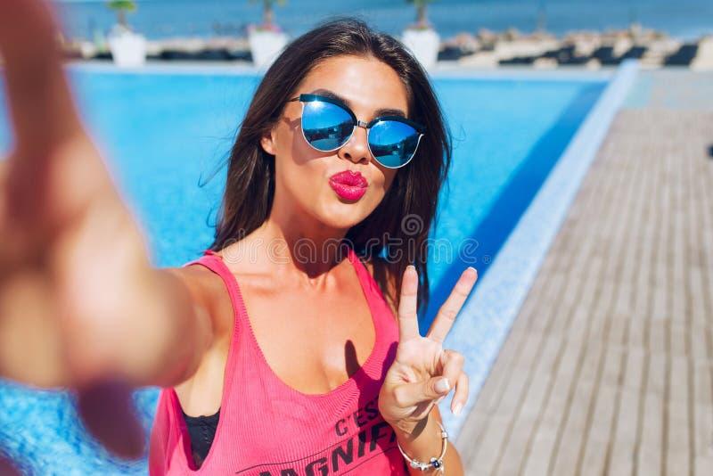 Selfie-retrato del primer de la muchacha morena atractiva con el pelo largo que coloca la piscina cercana Ella lleva la camiseta  foto de archivo
