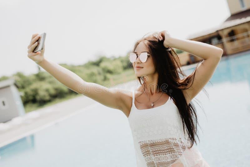 Selfie-retrato do close-up da menina moreno atrativa com o cabelo longo que está a associação próxima Veste o t-shirt cor-de-rosa fotografia de stock