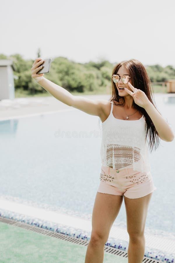Selfie-retrato do close-up da menina moreno atrativa com o cabelo longo que está a associação próxima Veste o t-shirt cor-de-rosa imagem de stock royalty free