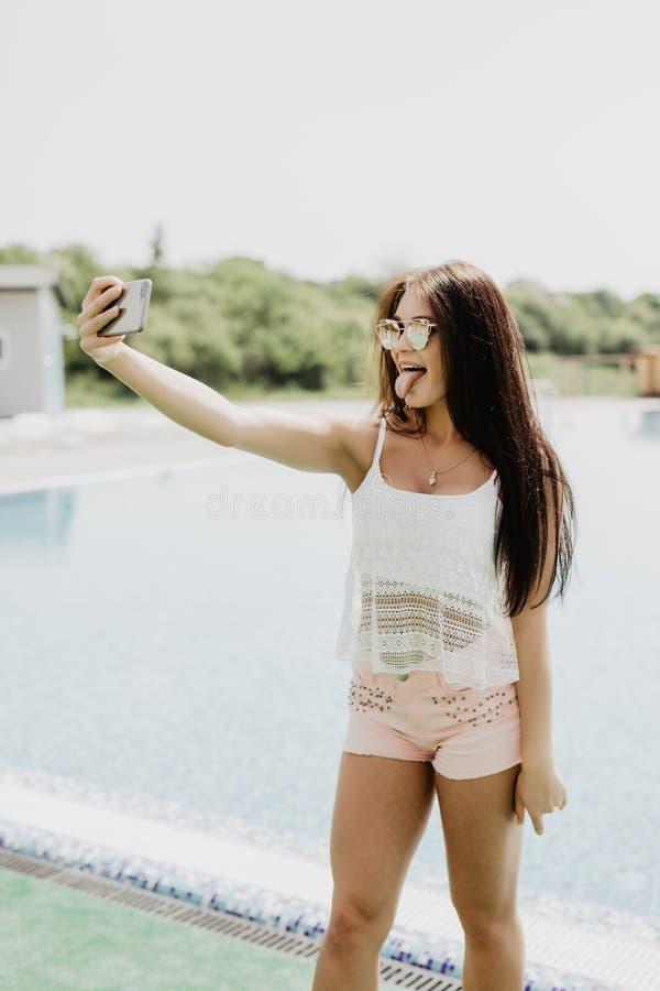 Selfie-retrato do close-up da menina moreno atrativa com o cabelo longo que está a associação próxima Veste o t-shirt cor-de-rosa fotografia de stock royalty free