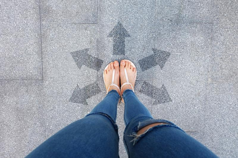 Selfie Shoes with Direction Arrows Choices. Woman Feet and Sandal Standing on Concrete Road Background. Great for Any Use stock photo
