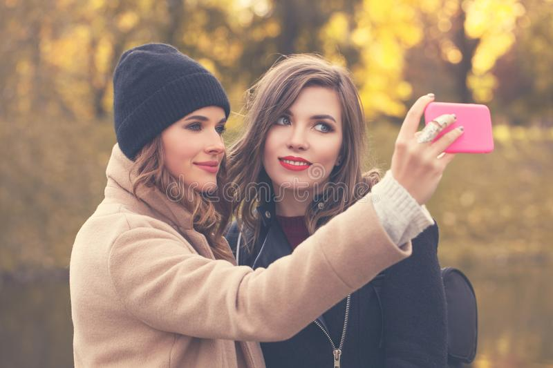 Selfie. Smiling Models with Cell Phone Taking Selfie. In Autumn Park. Fashion Women with Smartphone royalty free stock photos