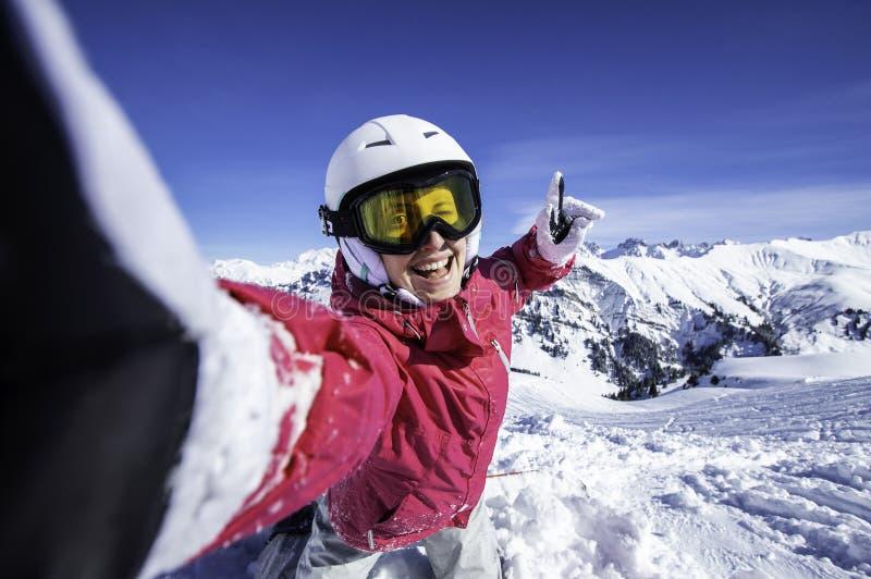 Selfie snowboarder Ung lycklig kvinna som tar selfie med smartphonen på överkanten av de norr fjällängarna, Frankrike arkivfoton