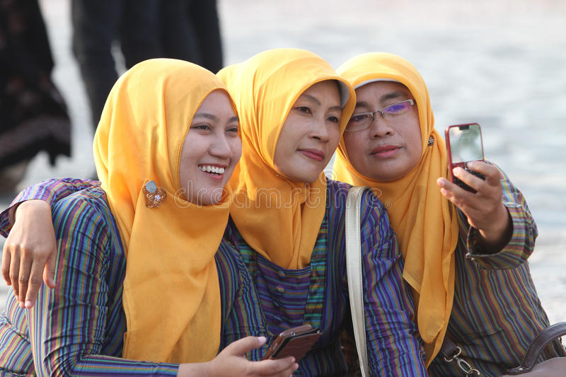 Selfie. Society is making a photo of himself with smartphone cameras in a public open space in Sragen, Central Java, Indonesia royalty free stock image