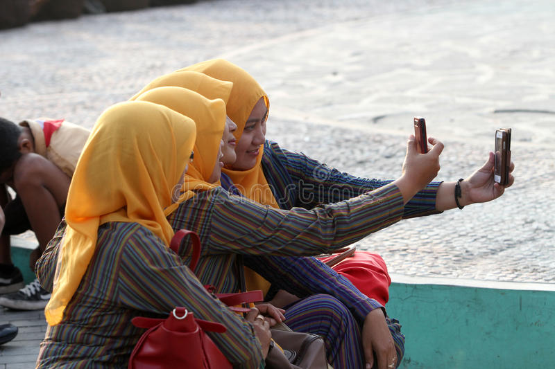 Selfie. Society is making a photo of himself with smartphone cameras in a public open space in Sragen, Central Java, Indonesia royalty free stock photography