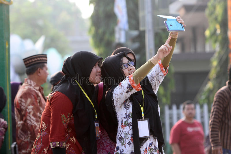 Selfie. Society is making a photo of himself with smartphone cameras in a public open space in Sragen, Central Java, Indonesia stock photo