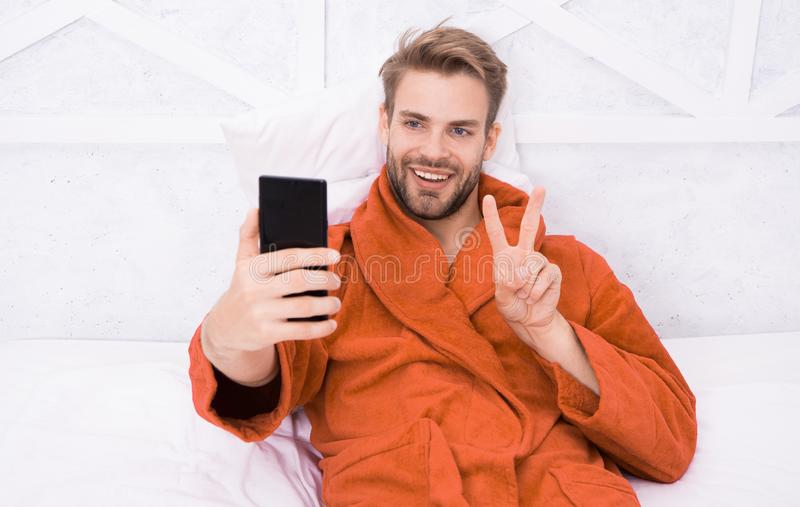 Selfie star. Happy man taking selfie with smartphone in bed. Handsome guy smiling with V hand gesture to selfie camera stock photos