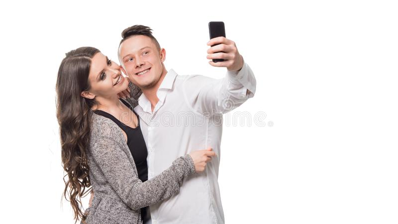 Selfie Tid Härliga unga par som kramar och ler, medan göra selfie som står över vit isolerad bakgrund arkivfoto