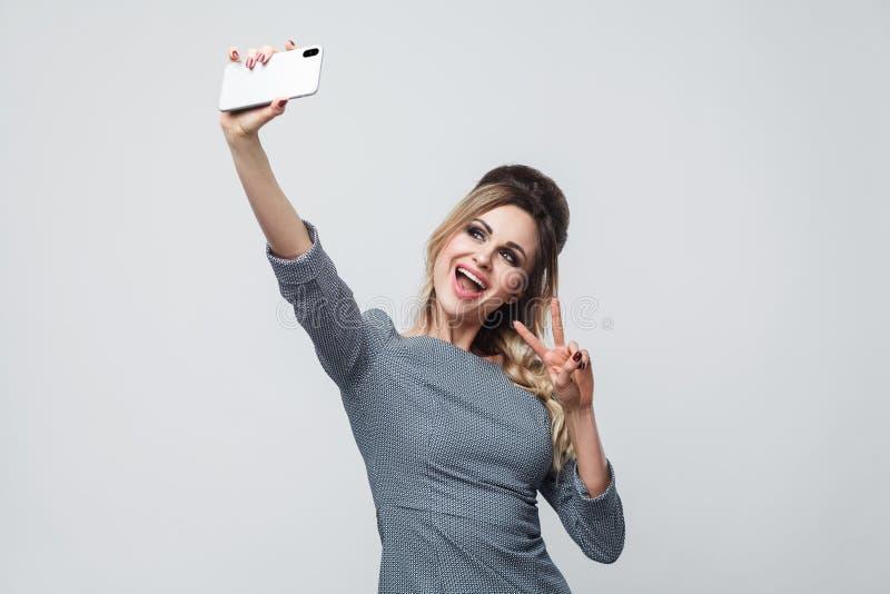 Selfie tid! Lycklig härlig bloggertonåring som bär i grå klänning med råttsvansen på huvudanseendet som visar v för att sjunga me royaltyfri bild