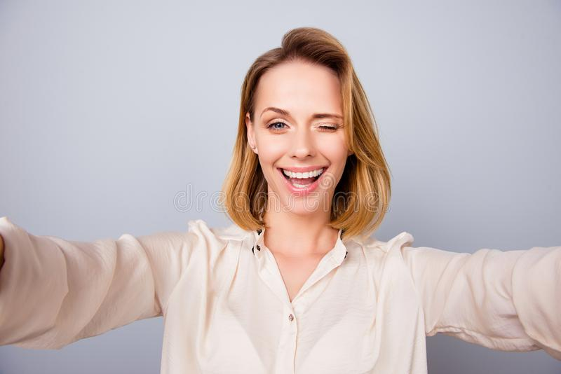Selfie time! Close up of attarctive young blond lady in a beige. Shirt, standing on the pure background and taking selfie on a camera of her device stock photo