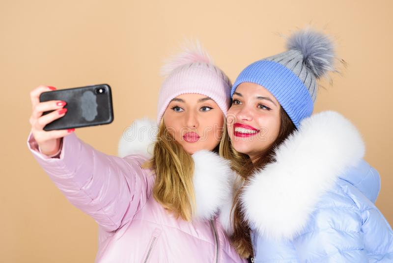 Selfie time. Emotional women in jackets. Friends hang out together. Female clothes shop. Modern trendy female outfit royalty free stock photography
