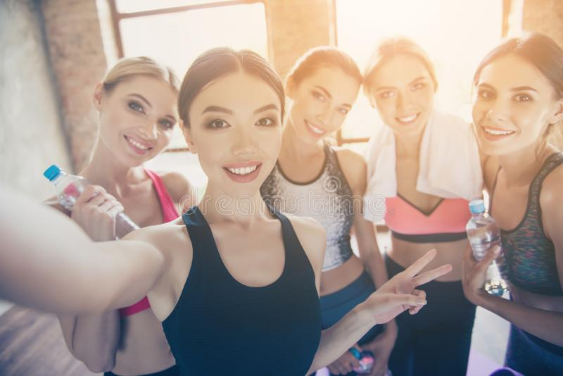 Selfie time, girls! Five girlfriends in fashionable sport outfit royalty free stock photos