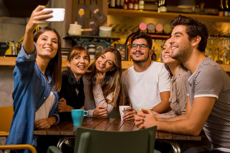 Selfie time. Group of friends taking a selfie at the cafe royalty free stock image