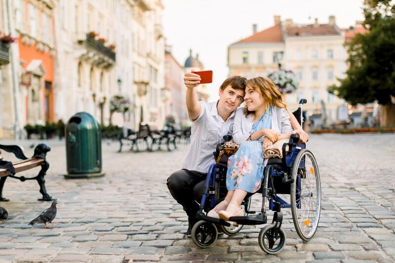 Selfie time. Handsome happy young man hugging his disabled young pretty woman and smiling while taking selfie with her. Selfie time. Handsome happy young men royalty free stock photography