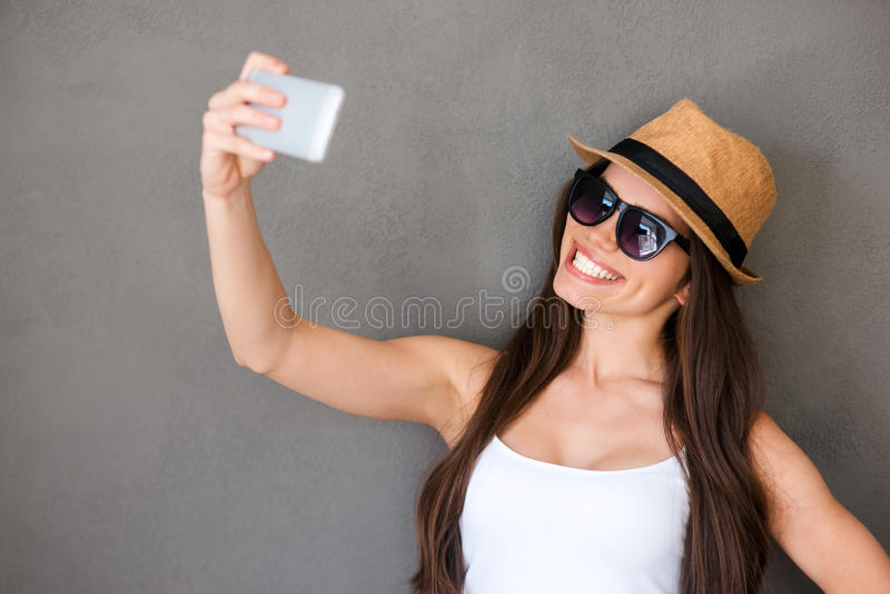 Selfie time. Joyful young woman making selfie by her smart phone and smiling while standing against grey background stock image
