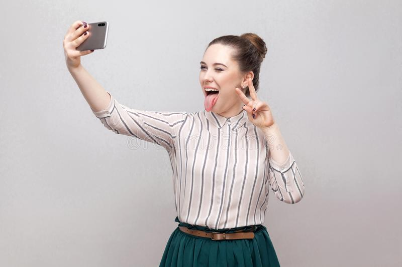 Selfie time! Portrait of happy foolish joyful attractive blogger woman wearing in striped shirt standing, winking and showing royalty free stock images