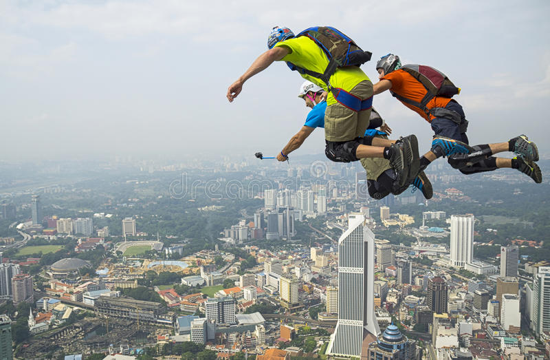 Selfie time on the sky. KUALA LUMPUR, MALAYSIA - SEPTEMBER 27: A BASE jumpers in jumps off from KL Tower at September 27, 2014. Their are an experienced BASE stock image