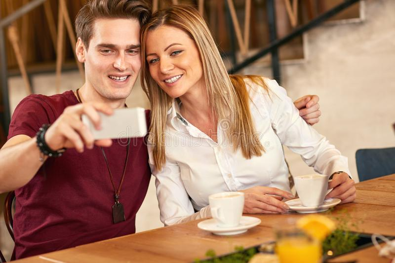 Selfie together in restaurant. Male and smiling female making selfie together in restaurant royalty free stock images