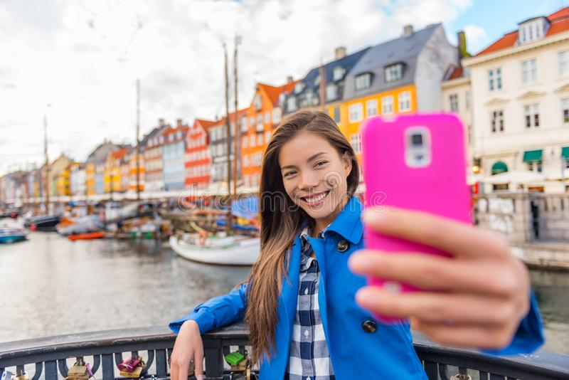 Selfie tourist girl taking photo with phone at Copenhagen Nyhavn, famous Europe tourism attraction. Asian woman visiting the old stock photo