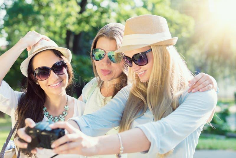 Selfie Tre attraktiva flickor som tar bilden på sommarferier fotografering för bildbyråer