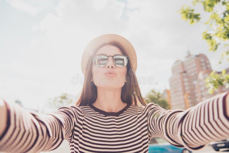 Selfie und ein Luftkuß! Junge nette Dame ist das Fotografieren im Freien lizenzfreie stockfotos
