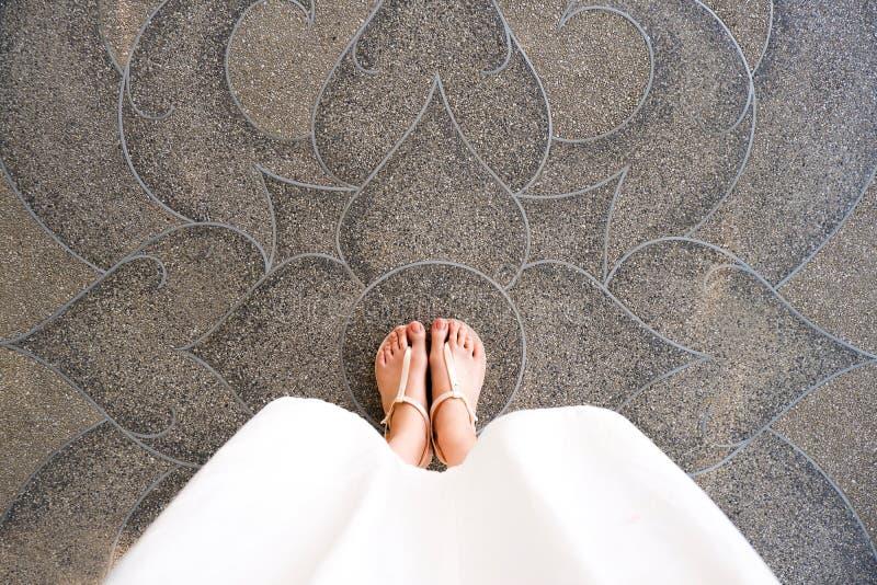 Selfie ung kvinna av fot i modeskor på konkret golv Det härliga flickaanseendet är foten & slanka ben som över ses från på vägen royaltyfri foto