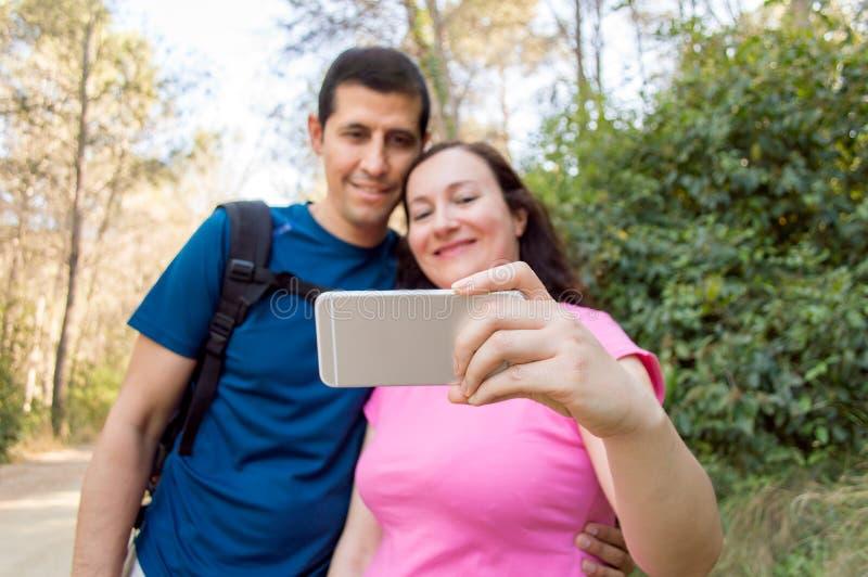 Selfie van paar die pret in het bos hebben stock afbeelding