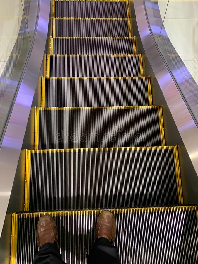 Selfie von Mannfüßen in den braunen Schuhen auf Rolltreppenschritten im Flughafen stockbild