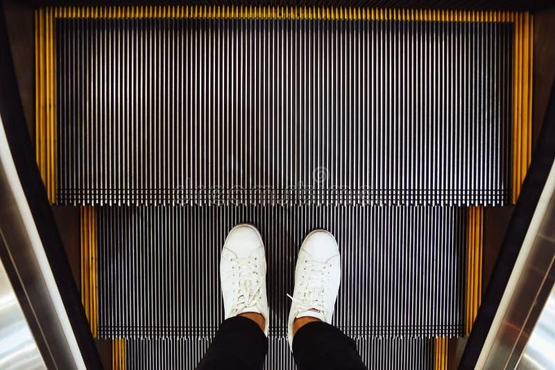 Selfie von Mannfüßen in den weißen Turnschuhschuhen auf Rolltreppenschritten in der Draufsicht des Einkaufszentrums in der Weinle lizenzfreies stockbild